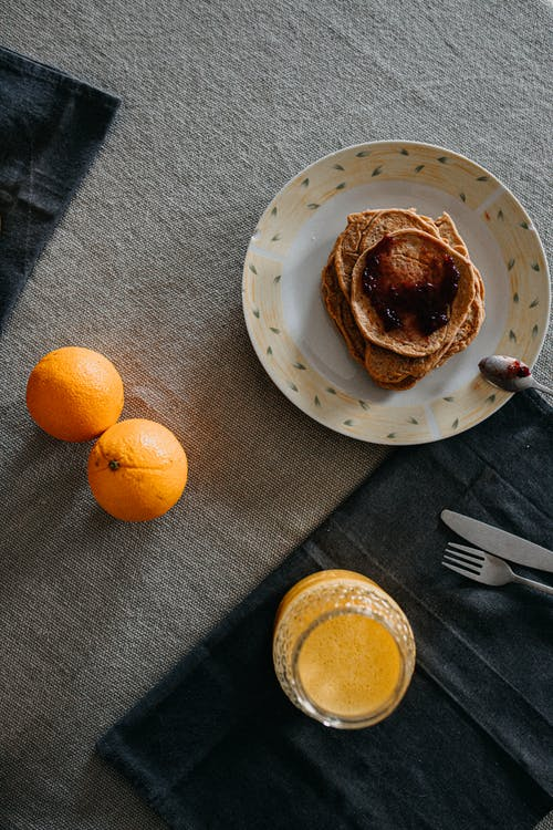 Orange Fruit on White Ceramic Plate Beside Stainless Steel Fork
