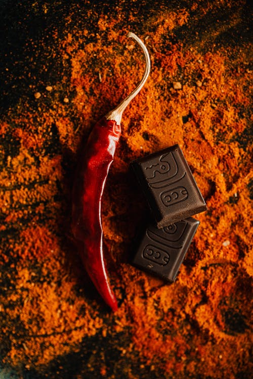 Red pepper with chocolate placed on table with spice
