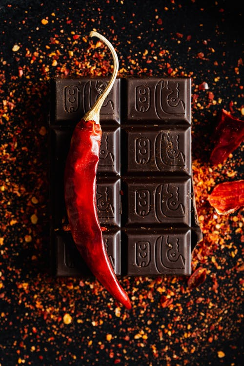 Top view of dry chili pepper placed on dark chocolate bar on dark table with ground spice