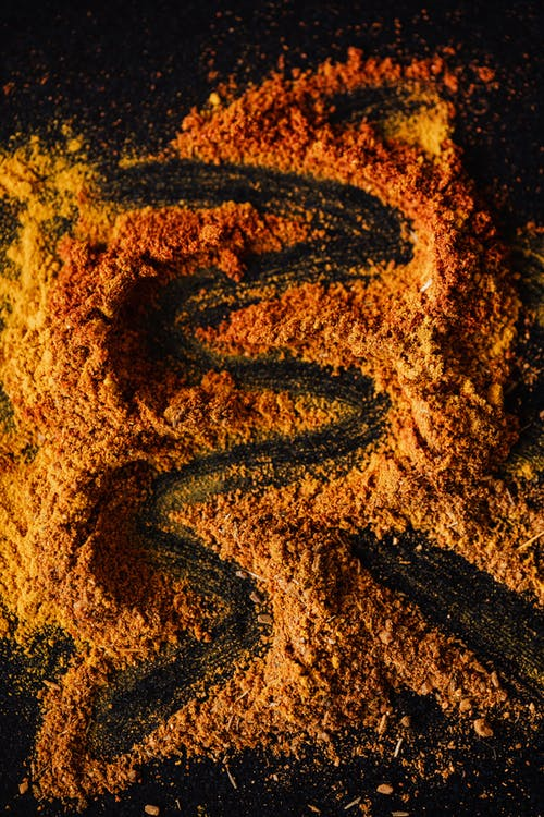 Mix of colorful powdered spices on black background