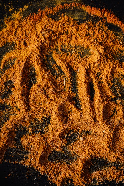 Heap of colorful dried spices on black surface