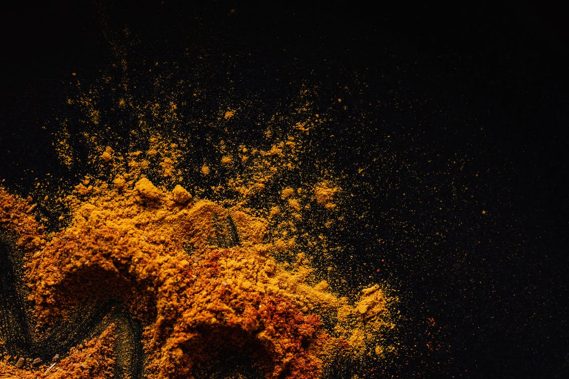 Composition of multicolored ground spices spilled on black background