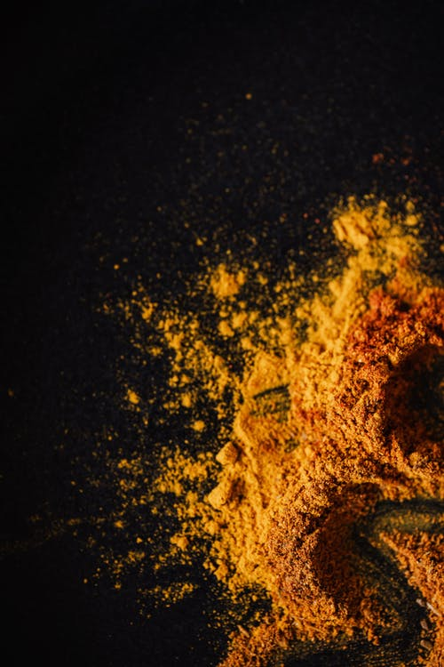 Top view of heap of colorful dry seasonings made of turmeric and smoked paprika with mix of peppers on black background