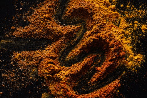 From above of creative design of smoked ground paprika and turmeric mixed together on black surface