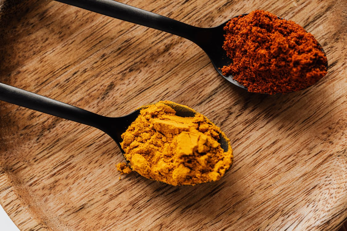 Ground turmeric and hot paprika on cutting board