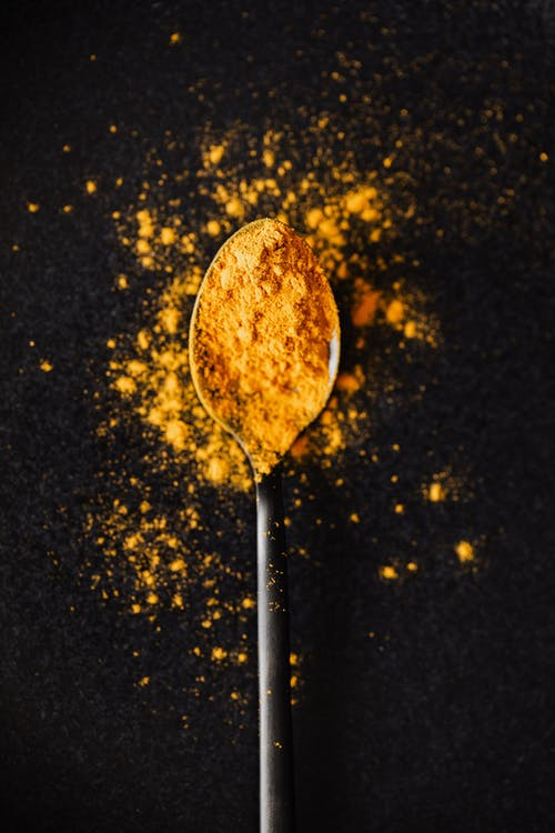 Curcuma powder on tablespoon and spilled on black surface
