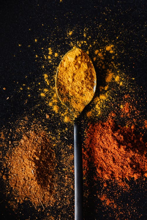 Pile of dry spices with colorful turmeric on tablespoon
