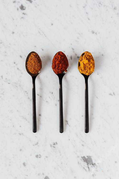 Assorted multicolored dry spices on spoons on table