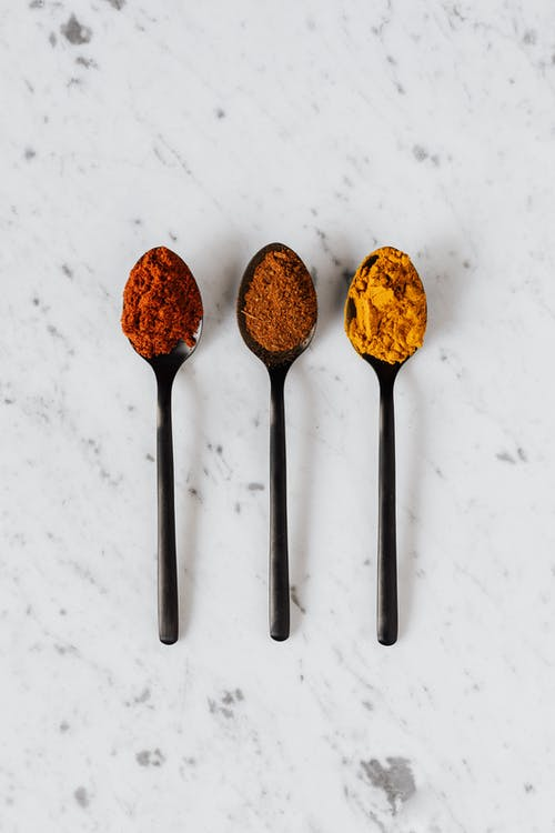 Different colorful dry seasonings on spoons on table
