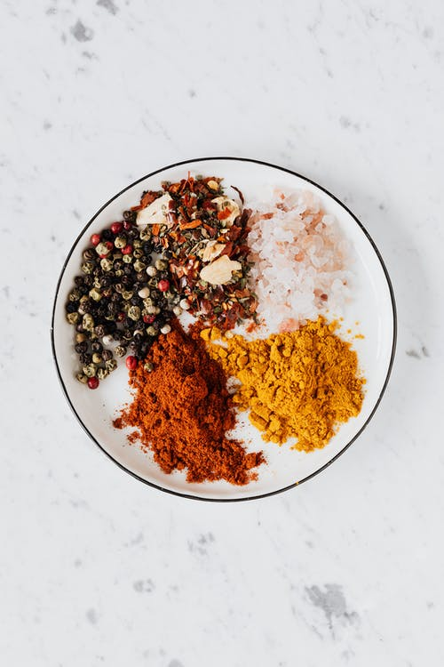 From above of bowl filled with piled of turmeric and paprika powder near mix of pepper flakes and seeds with sea salt on table