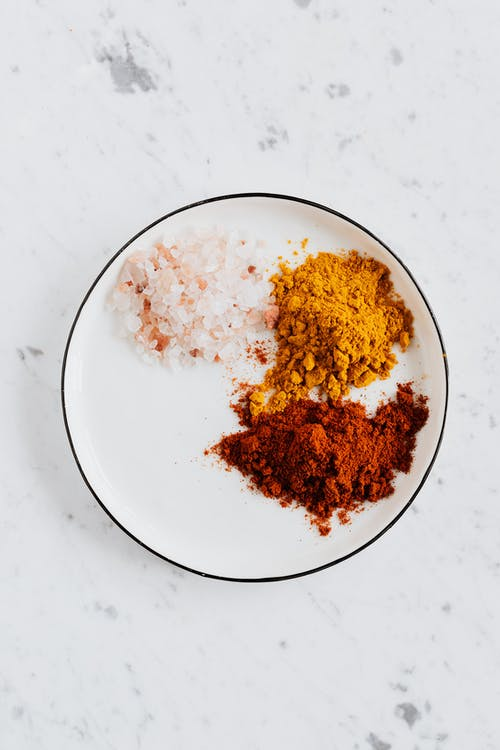 Top view of different powdered spices of curcuma and chili with pink salt in metal bowl on white marble surface