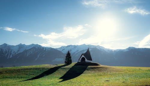 Green Grass Field Near Mountain Under White Clouds