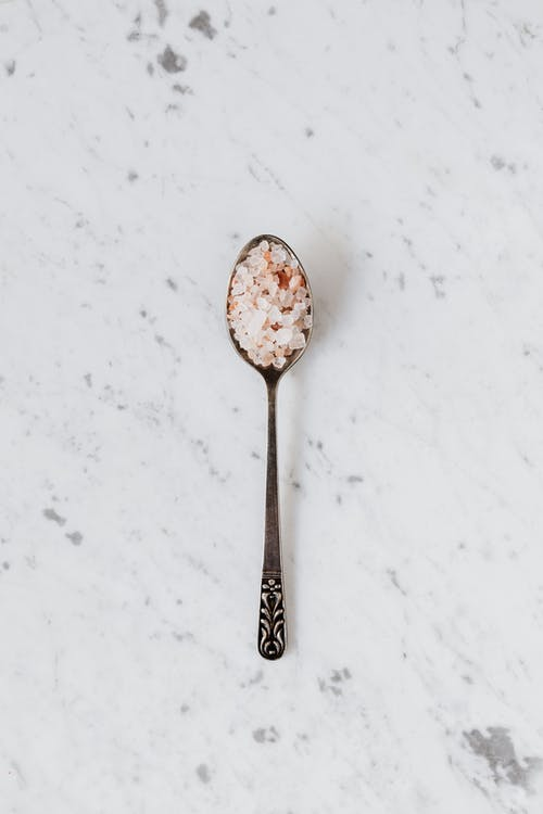 Top view of metal teaspoon with mix of salt and curcuma on smooth marble surface