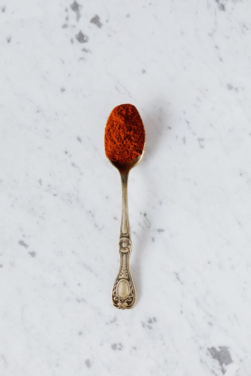 Silver spoon with red paprika powder