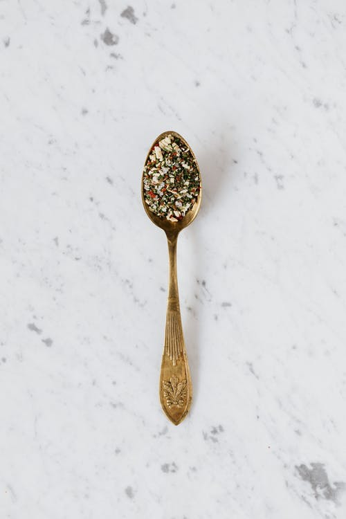 Top view of metal spoon filled with mixed herbs and spices used for healthy gourmet food preparing placed on marble surface