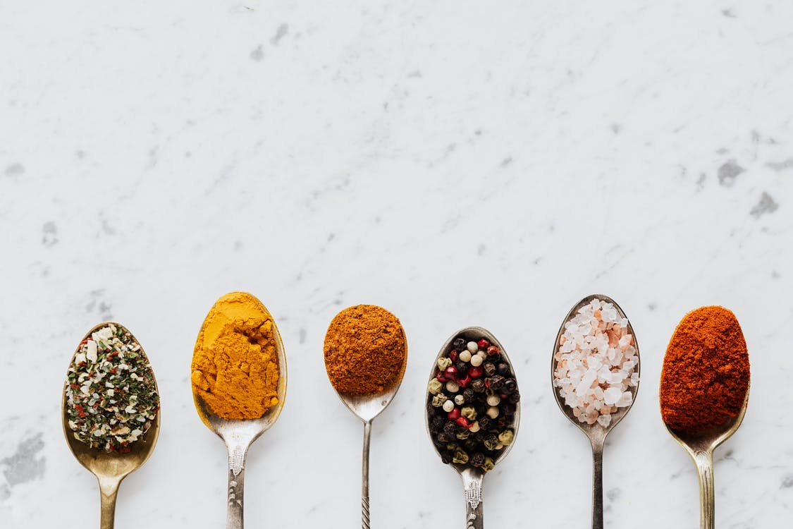 Top view of assorted aromatic condiments arranged together in metal spoons on marble surface used for delicious gourmet meal cooking