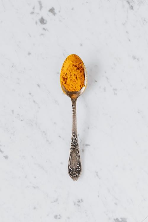 Top view of metal spoon with dry curcuma powder used for healthy gourmet food preparing placed on marble surface