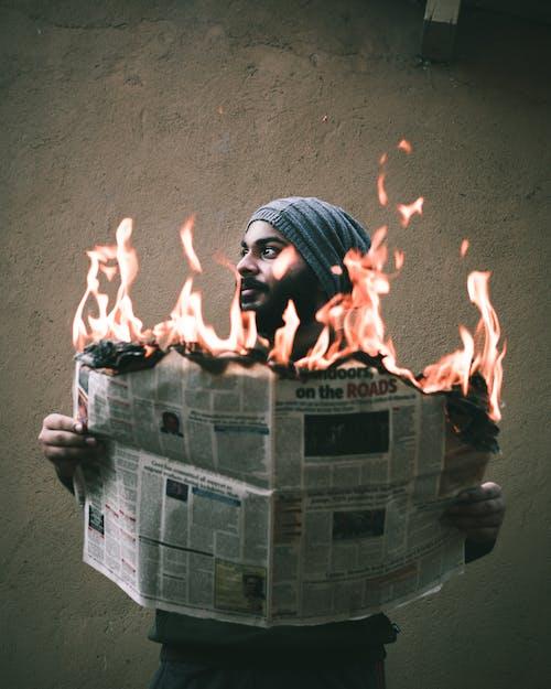 Bearded ethnic man burning newspaper near cement wall