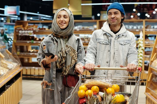 Couple with a Shopping Cart Buying Groceries