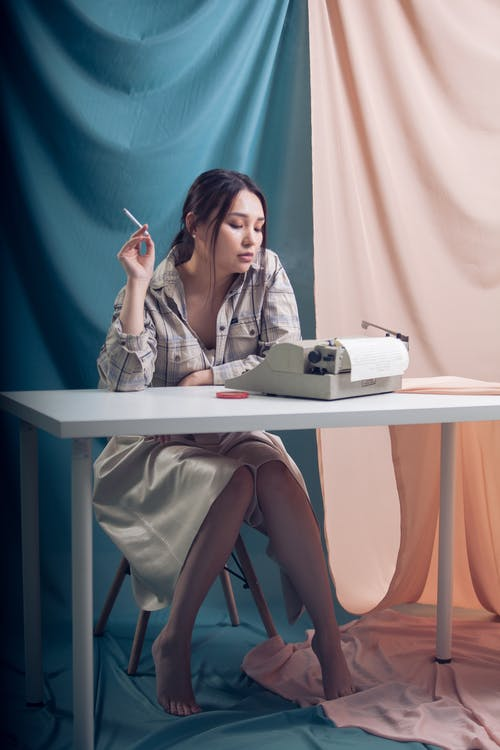 Stylish woman with cigarette sitting at table with retro typewriter