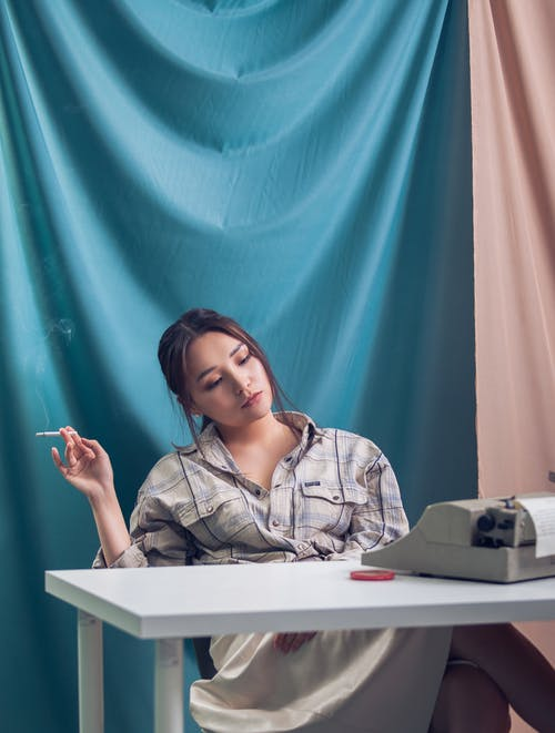 Pensive young female in casual wear sitting at white table near blue and pink drapery while smoking cigarette