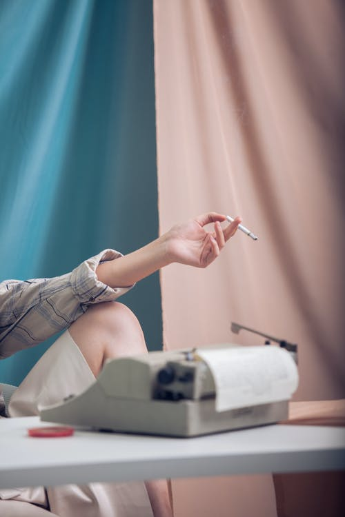 Unrecognizable female sitting at white table with typewriter near blue and pink curtain while holding cigarette in hand