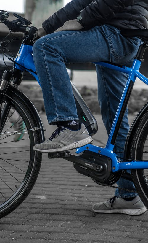Person in Blue Denim Jeans Riding Blue Bicycle