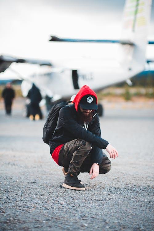 Bearded male traveler hunkering down near light aircraft