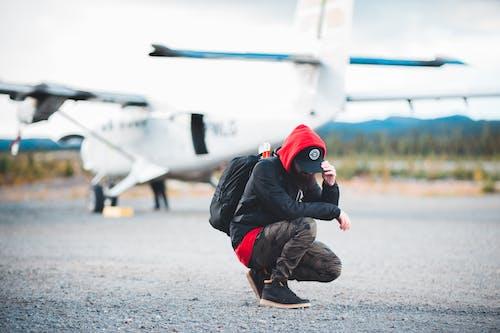 Unrecognizable male traveler hunkering down near modern light jet