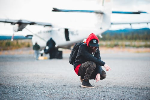 Male backpacker hunkering against contemporary private jet