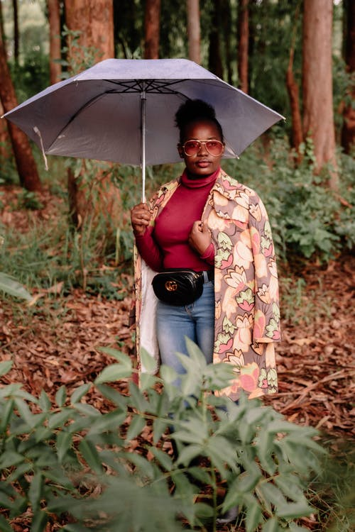 Attractive African American female wearing trendy outfit and coat standing under umbrella amidst green lush trees in forest and looking away calmly