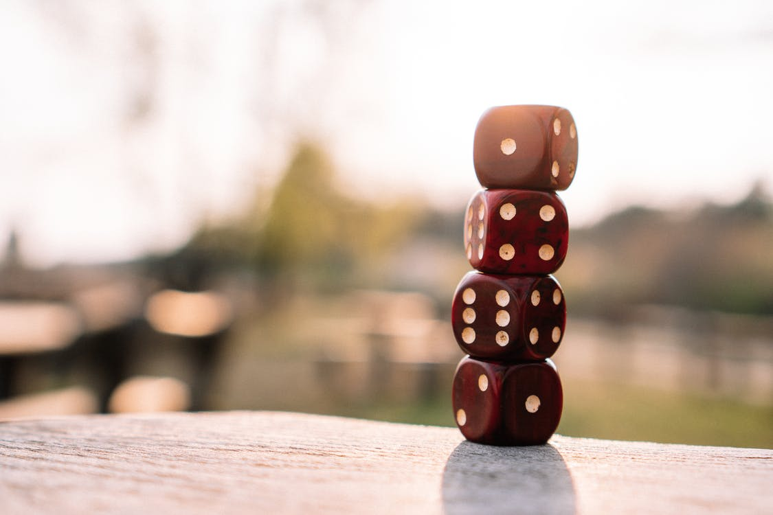 Set of red dice stacked together on wooden table placed on sunny terrace in daylight