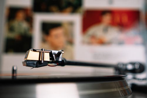 Vintage vinyl record player placed on table against wall with blurred photos of musicians in light living room