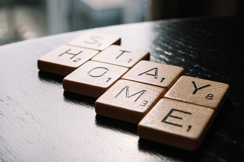 High angle of scrabble letter tiles arranged on black wooden table in inscription Stay Home in living room