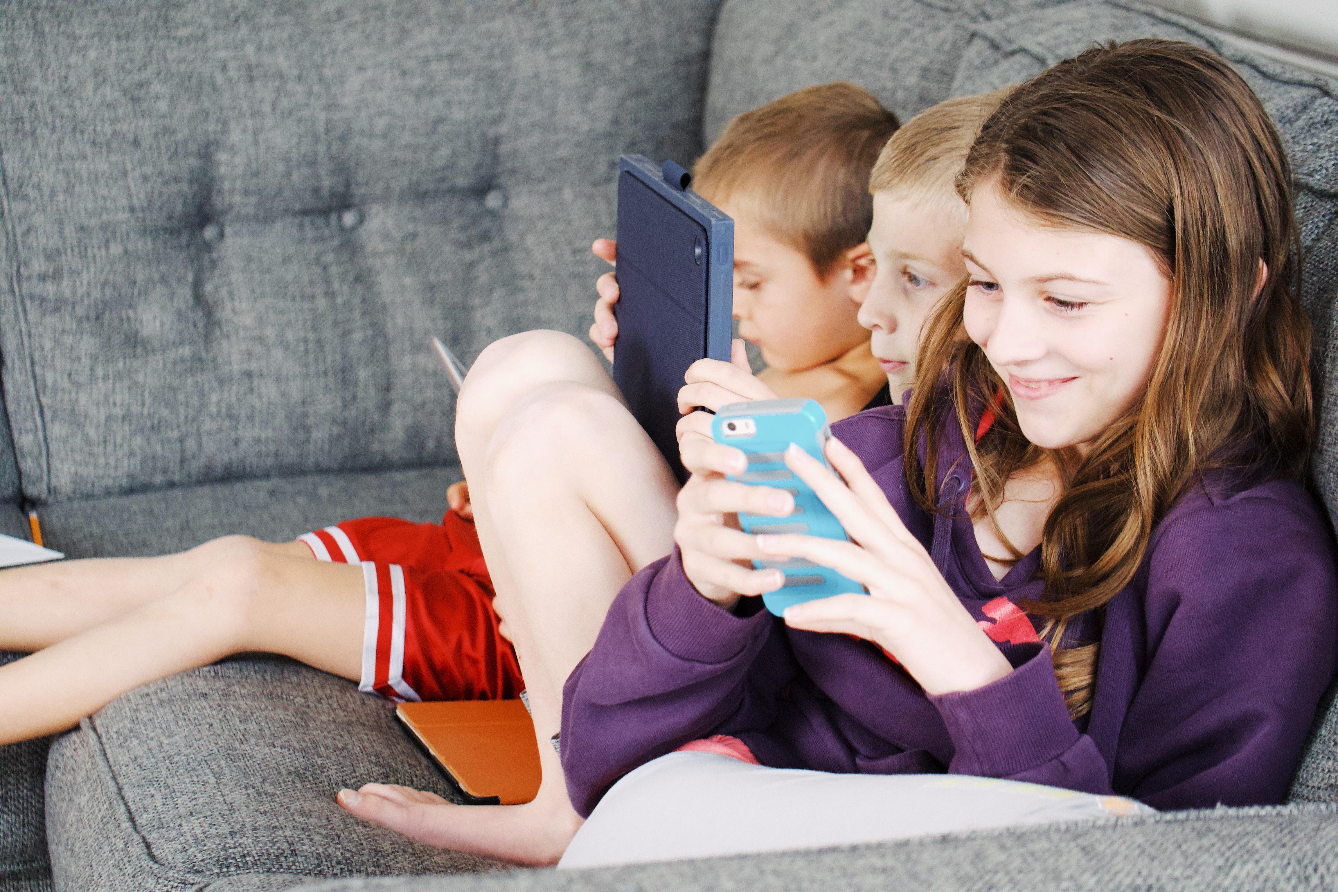 Photo of Kids Sitting on Gray Sofa · Free Stock Photo