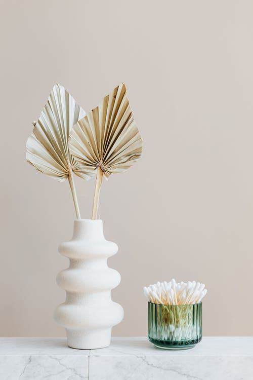 Vase with decorative leaves and container with cotton buds