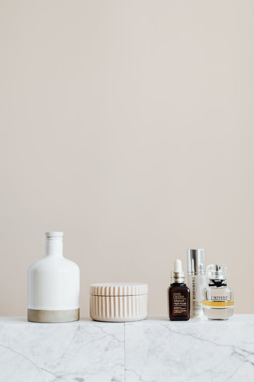 Reusable cosmetic containers for cream and shampoo arranged near various skincare products and perfume bottle on white marble shelf against beige wall in elegant bathroom interior