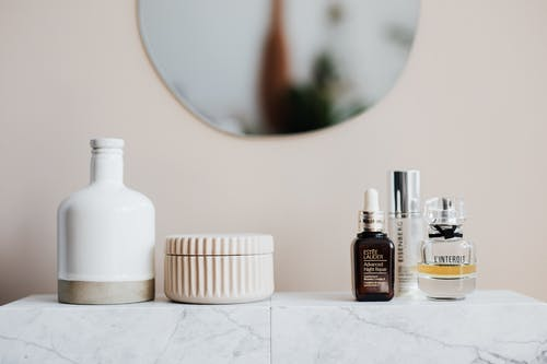 Various beauty products on ceramic shelf in bathroom
