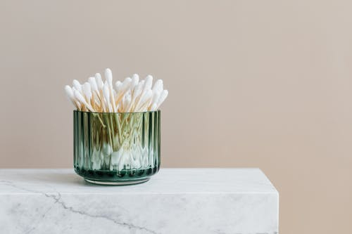 Photo of White Cotton Buds in Glass Container