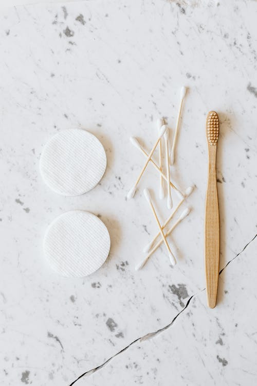 Cotton pads and buds with wooden toothbrush on marble surface