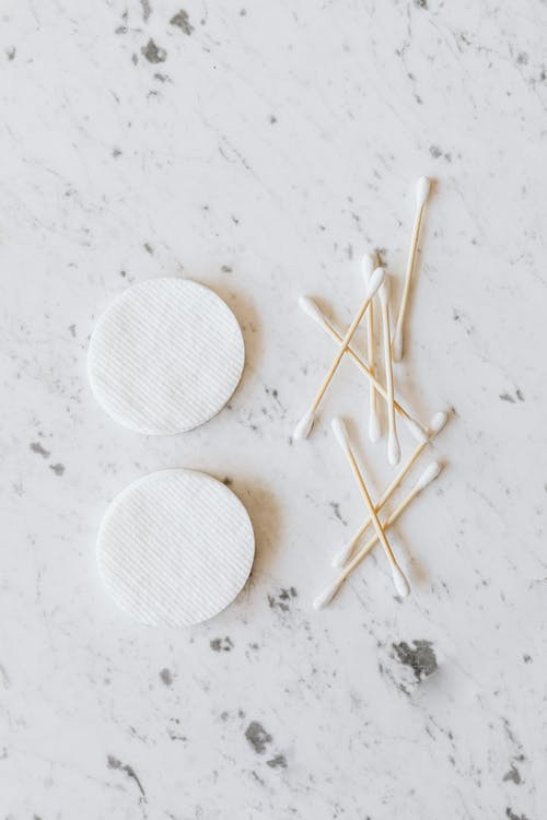 Set of cotton buds and pads on marble surface