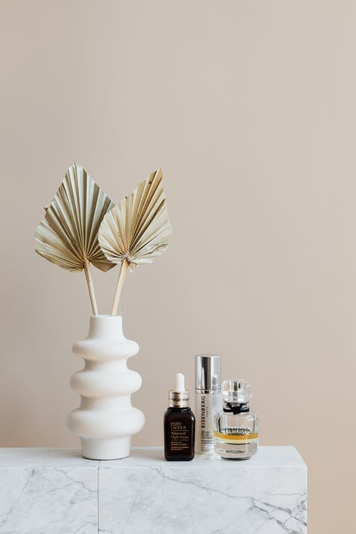 Set of beauty products with artificial branches in vase