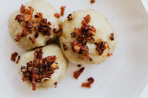 Round cepelinais with bacon served on plate