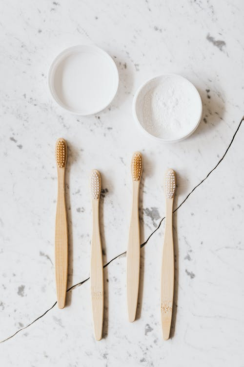 Set of toothbrushes and tooth powder on chipped table