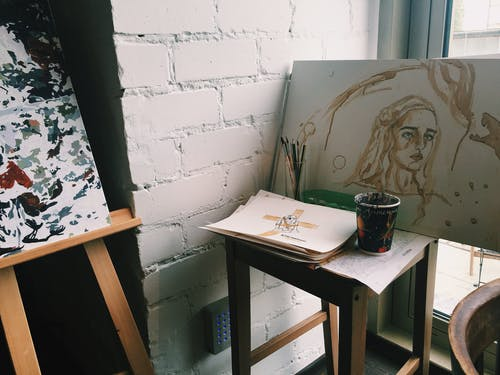 Creative artist workplace with drawings on easel