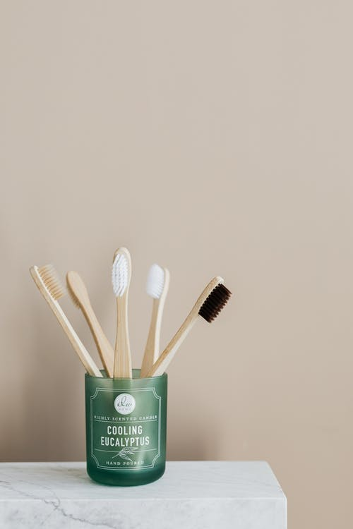 Bamboo toothbrushes in green holder on marble table