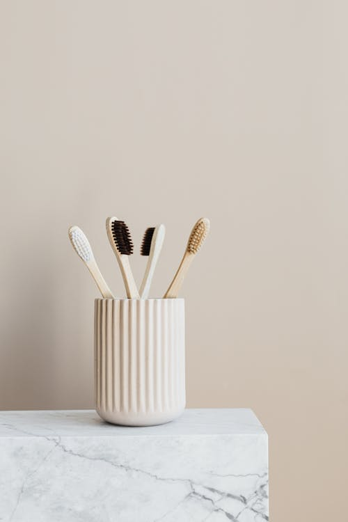 Set of natural wooden toothbrushes in white holder