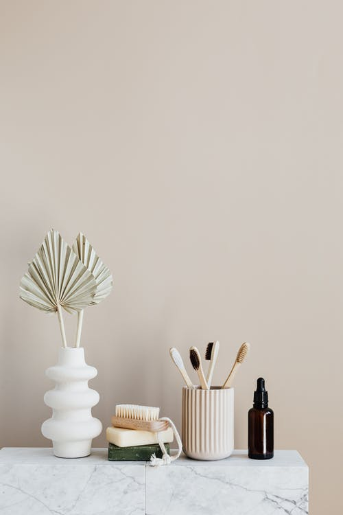 White creative vase with decorative artificial plants and organic soap with body brush placed near set of bamboo toothbrushes in ceramic holder and dark glass reusable bottle of lotion