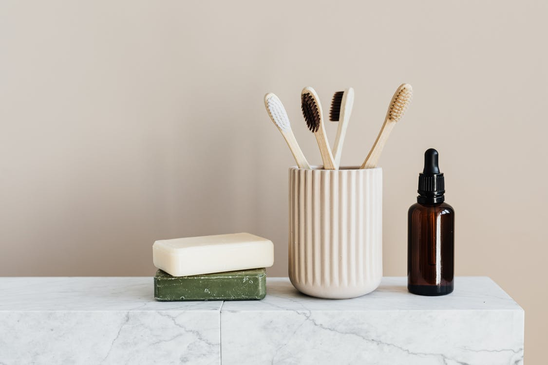 Collection of organic soaps and bamboo toothbrushes in ceramic minimalism style holder placed near renewable glass bottle with essential oil on white marble tabletop against beige wall