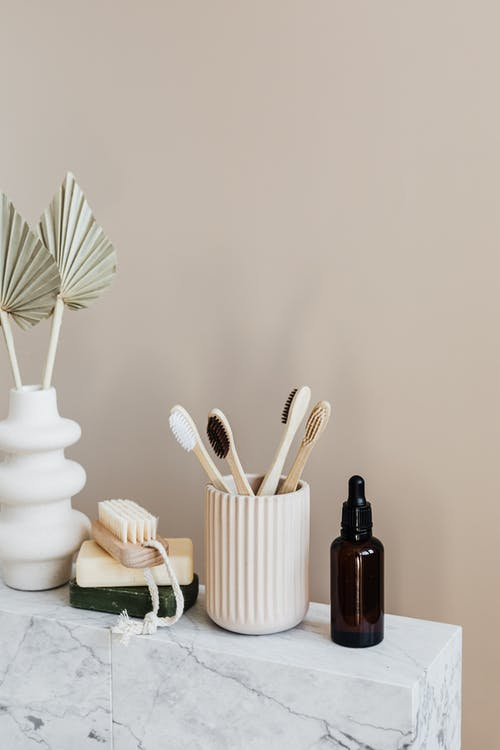 Collection of bamboo toothbrushes and organic natural soaps with wooden body brush arranged with recyclable glass bottle with natural oil and ceramic vase with artificial plant